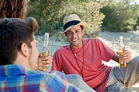 Young friends sitting on sand with beer