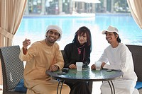 Middle Eastern people sitting at table outdoors