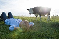 Woman relaxing in field with cow