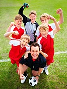 Excited soccer team with coach cheering