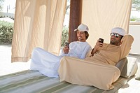 Two Middle Eastern men sitting on bed