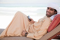 Middle Eastern man with mobile phone on sun lounger