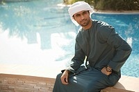 Middle Eastern man sitting by swimming pool, portrait