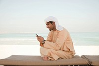 Middle Eastern man sitting on sun lounger with mobile phone