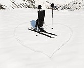 Heart shape in snow with woman skier