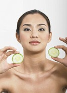 Young woman holding cucumber slices