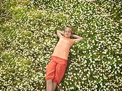 Child lying in field of daisies