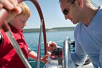 Man explaining boy compass on yacht