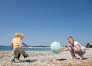 Mother with twins at beach playing ball