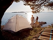 Couple with tent by sea