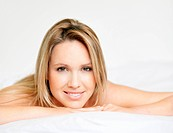 Woman lying relaxed in bed with a smile