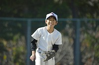 Boy in a baseball uniform smiling at camera