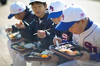 Boys in baseball uniform having lunch, sitting on bench