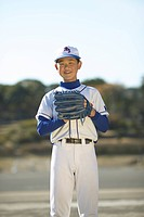 Portrait of boy in baseball uniform in field, smiling