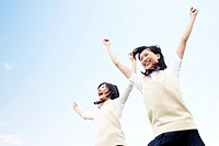 Two Japanese Schoolgirls Leaping in the Air and Laughing