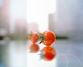 Two Cherry Tomatoes on a Reflective Surface in Front of a Window