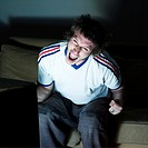 pictures in a living room a funny and expressive man sitting on a couch watching on tv sport event