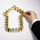 Businessman creating arrow symbol with gold dominoes
