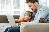 Son and father using computer