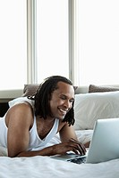 Man relaxing in bed with a laptop (thumbnail)