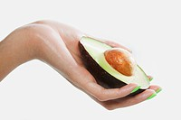 Woman holding sliced avocado (thumbnail)