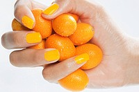 Woman holding handful of kumquats