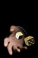 Man rolling gold dice
