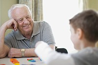 Man looking at grandson play with plastic letters (thumbnail)