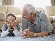 Boy and grandfather lying on floor and laughing (thumbnail)
