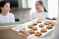 Woman holding a tray of fresh chocolate chip cookies (thumbnail)