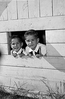 Twin brothers looking through window of wooden playhouse