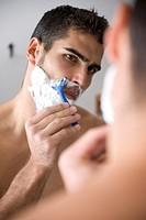 Young man shaving.