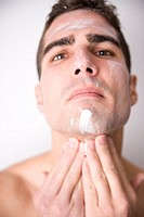 Young man applying facial cream.