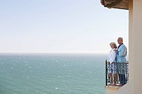 Senior couple in bathrobes on balcony overlooking ocean