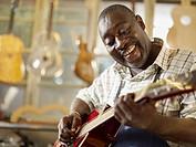 Black craftsman playing guitar in workshop