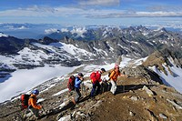 Four mountain hikers ascending to mount Hochfeiler, Zillertal Alps, South Tyrol, Italy