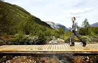 Young woman walking on a timber bridge above a river, Rimstigen, Naerofjord, Sogn og Fjordane, Norway, Scandinavia, Europe