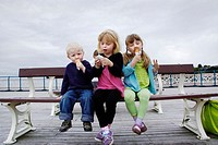 3 year boy, 7 year girl and 6 year girl sitting on bench at seaside eating ice creams