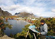 Norwegian painter in front of the coastal village Reine, Lofoten, Norway, Scandinavia, Europe