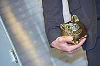 Man in front of safe deposit boxes holding golden piggy bank, close_up