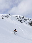 A male snowmobiler enjoys fresh powder in the Monashee mountain range, North Thompson region near Valemount, British Columbia, Canada