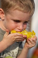 little girl eating corncob