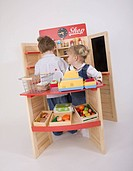 little boy and little girl playing in grocery shop for children