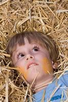little boy lying in straw