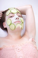 young woman with cucumber face mask