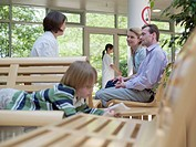 Couple consulting with female doctor at waiting area