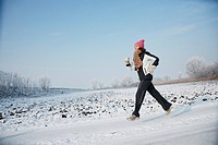 Woman running in snow covered landscape
