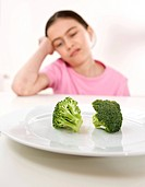 Girl disliking broccoli