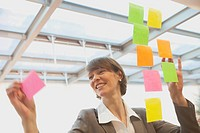 Business woman sticking post_its on a glass pane
