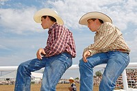 Two boys in cowboy outfit watching a rodeo